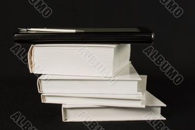 Stack of printed books with electronic book reader