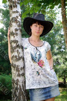 beautiful girl in the hat around birch