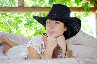 beautiful girl in the hat lying in the open air