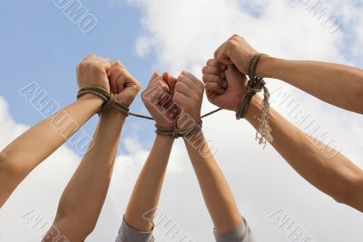 Three pairs of human hands tied up together