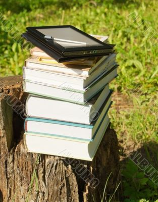 Stack of colorful books with e-book reader