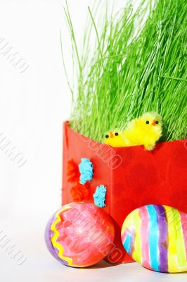 Colored easter eggs and chickens in green grass