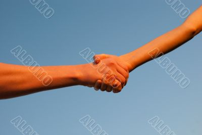 Hands shaking each other against blue sky