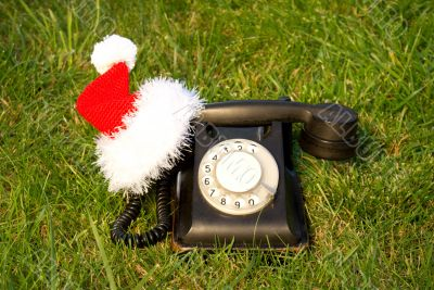 Old fashioned black telephone with Santa`s hat