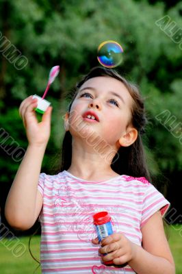 The little girl starts up soap bubbles