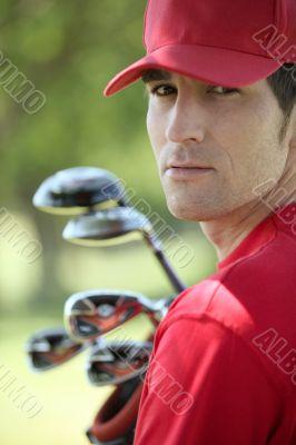 Golfer holding golf clubs.