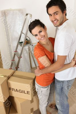 Couple with packing boxes marked fragile