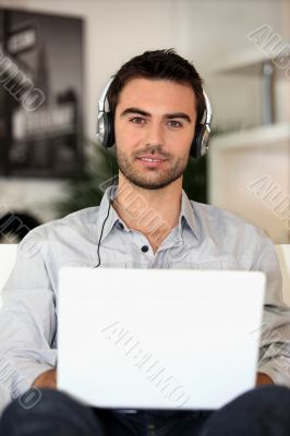 young music lover with earphones and laptop