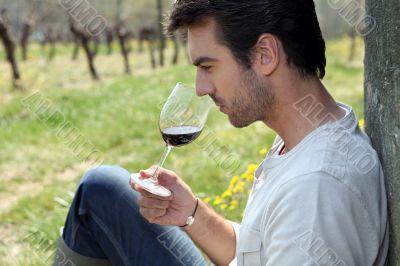 Man tasting wine in field