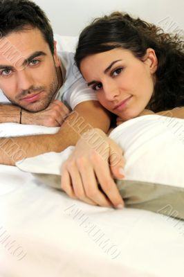 Attractive couple lying in bed