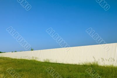 Long white metal fence