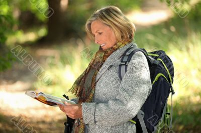 Older woman looking at a map in a forest