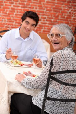 Woman enjoying a meal out with her grandson