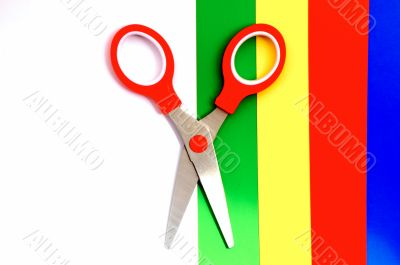 Colorful paper with child`s scissors