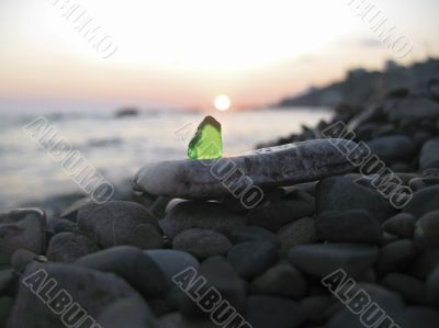 Green glass laying on the sea shore