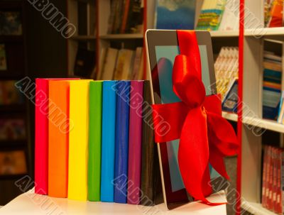 E-book tied up with red ribbon and row of books