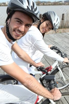 Young couple cycling alongside a river