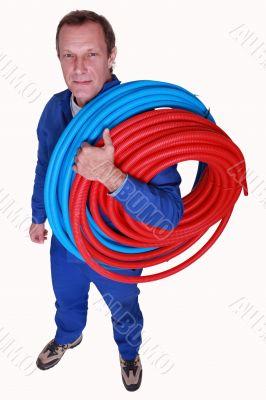 Studio shot of plumber with reels of tube