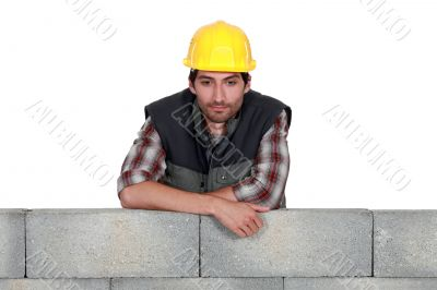 Young mason leaning on a wall