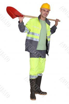 Man holding spade over shoulder