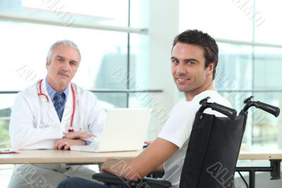 Young man in a wheelchair talking to a doctor