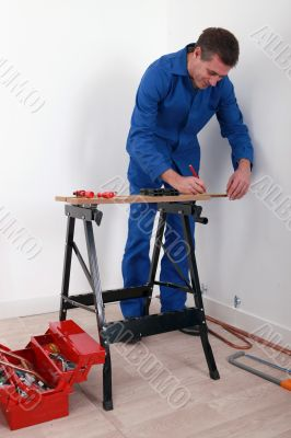 a craftsman tracing on a workbench