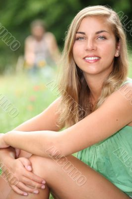 Young woman sitting in a meadow in the summertime