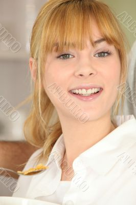 Blond girl eating cereals