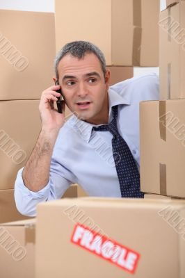 Cellphone user surrounded by boxes