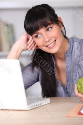 Woman working on her laptop and holding an apple