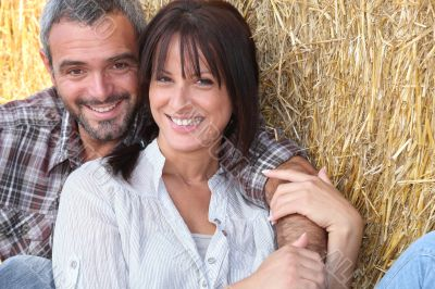 Farming couple sitting in the hay