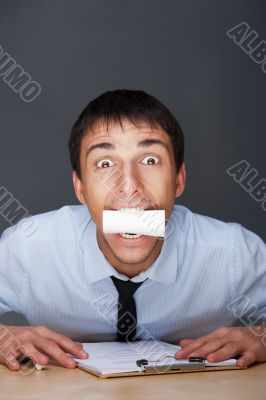 Closeup portrait of business man holding business card in his mouth