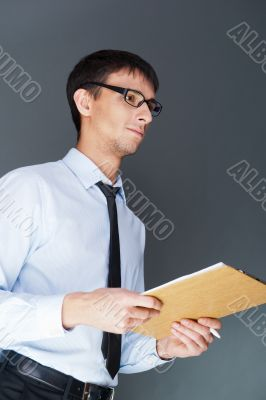 Closeup of a young smiling business man standing confidently against the wall