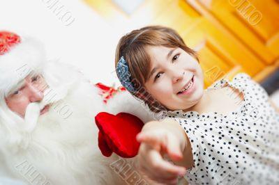 Christmas theme: Santa Claus and little girl having a fun.