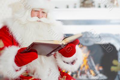Santa sitting at the Christmas tree, near fireplace and readingÑŽ