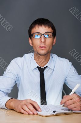 Portrait of an adult business man sitting in the office and signing documents.