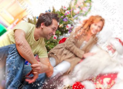 Happy family embracing and sitting on the floor in front of Christmas Tree.