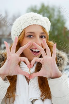 Portrait of beautiful young red hair woman outdoors in winter.