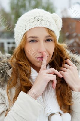 Portrait of young pretty woman in winter park.