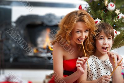 Mother and her daughter sitting together near christmas tree.