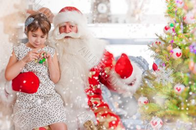 Christmas theme: Santa Claus and little girl having a fun.