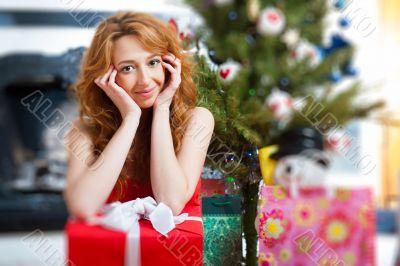 Christmas woman near a Christmas tree holding big gift box.