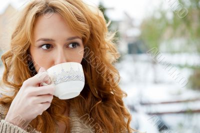 Portrait of beautiful red hair girl drinking coffee on winter background