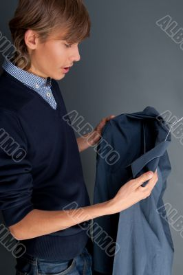 A portrait of a man trying choosing shirts over grey background