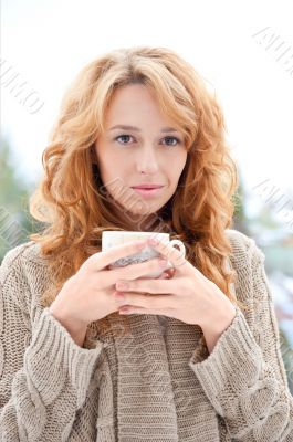 Portrait of young pretty red hair woman with cup of hot coffee o