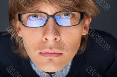 Satisfied young man with glasses looking at camera like at lapto