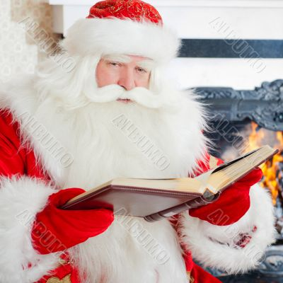 Santa sitting at the Christmas tree, fireplace and reading a boo