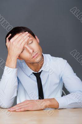 Closeup of a young business man having a stress. Headache. Again