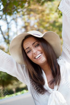 Portrait of sweet young woman enjoying at the park with raised h