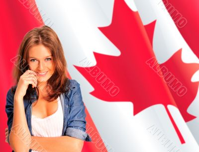 Portrait of a pretty young woman against a Canadian flag , smili